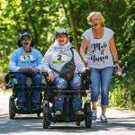 2 Frauen mit E-Rolli nehmen mit ihrer Begleitperson an einem Erlebnisrennen teil.