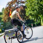 Ein Mann mit Beeinträchtigungen fährt auf seinem Fahrrad durch den Park.
