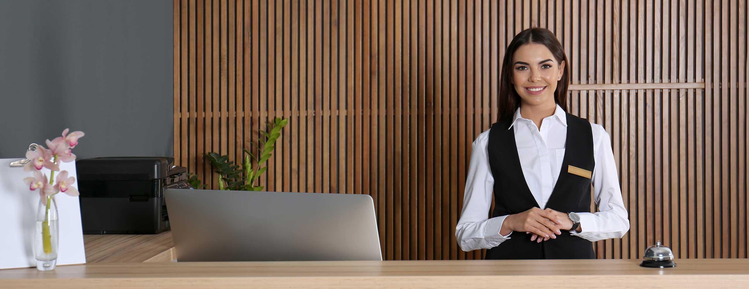 Portrait einer jungen Rezeptionistin am Schreibtisch in der Hotellobby