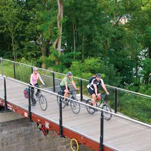 Drei Radfahrer auf einer Waggonbrücke am Panoramaradweg Niederbergbahn
